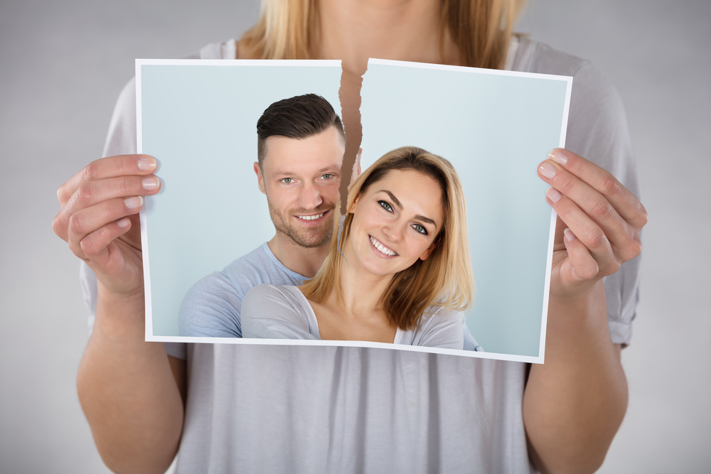 woman tearing up photo with her ex