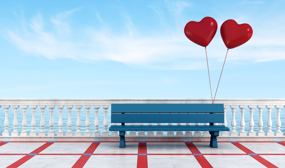 Bench with two heart-shaped balloons on the waterfront